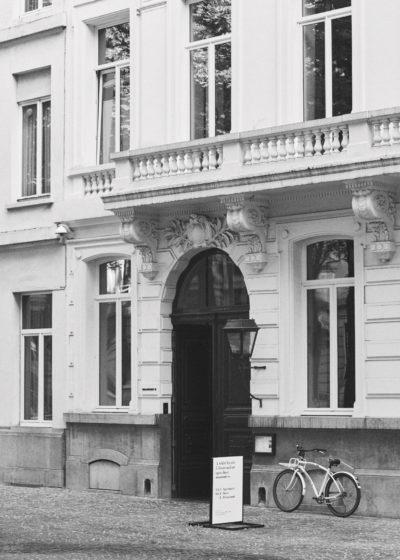 A white facade, five floors and an open door. by Graanmarkt 13