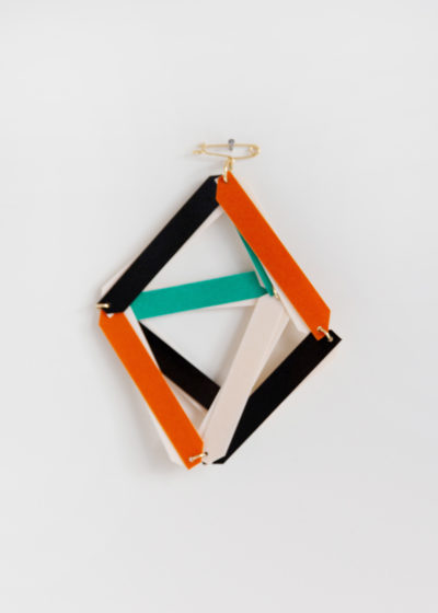 Graphical pin in lacquered paper by Ingrid Verhoeven
